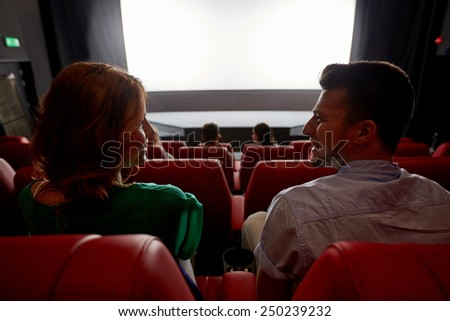 cinema, entertainment and people concept - happy friends watching movie in theater from back - stock photo