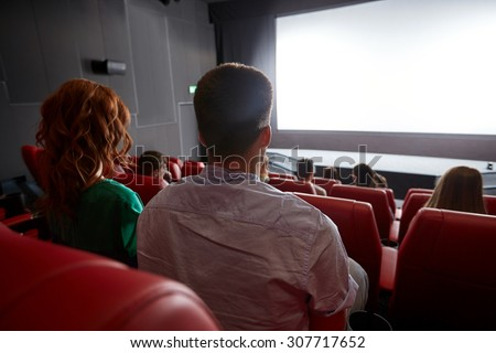 cinema, entertainment, leisure and people concept - couple watching movie in theater from back - stock photo