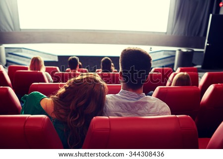 cinema, entertainment, leisure and people concept - happy, couple watching movie in theater from back - stock photo