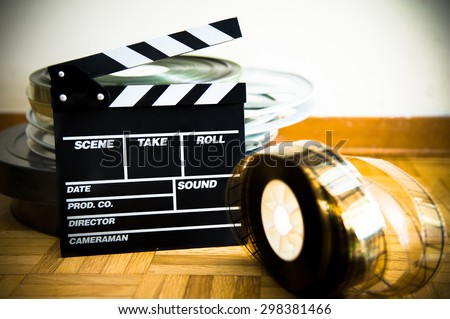 Cinema movie clapper board and 35 mm film reel on wooden floor selective focus - stock photo