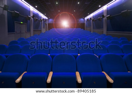 cinema or theatre empty seats with projecton light - stock photo