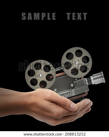 cinema projector old-fashioned. Man hand holding object isolated on black background. High resolution