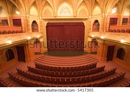 cinema stage with red velvet curtains and  empty chairs in the foreground - stock photo