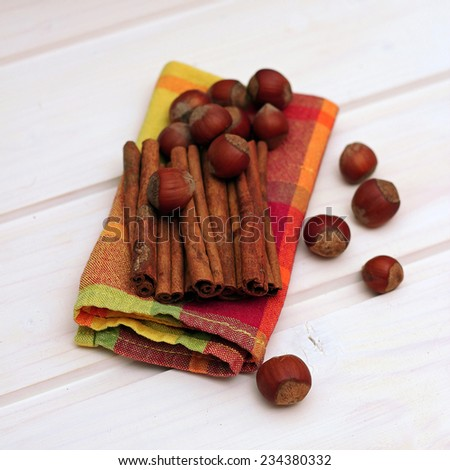 Cinnamon and hazelnuts with napkin on a white wooden background. Selective focus - stock photo