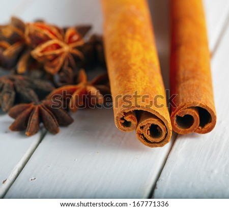 Cinnamon and star anise over white wooden background - stock photo