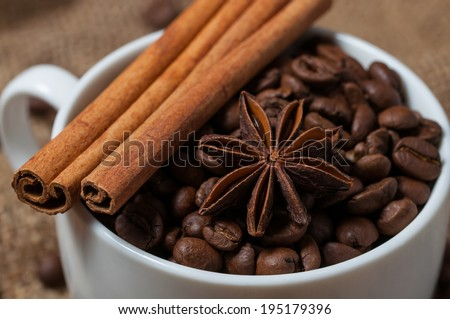 Cinnamon, aniseed and coffee beans in the coffee cup. - stock photo