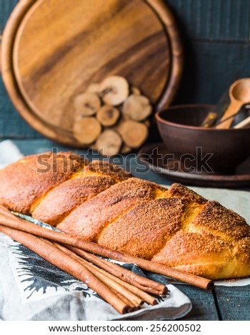 cinnamon bun browned crust, sweet pastries on a blue background - stock photo