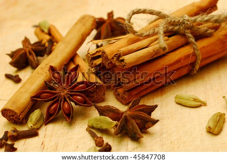 cinnamon , cardamom,cloves and star anise on a wooden board - stock photo