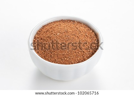 Cinnamon ground in a white bowl on white background.  As a spice or condiment cinnamon sold in the form of sticks or a hammer. Used as a spice in cuisines all over the world.