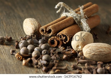 Cinnamon, nutmeg, allspice and cloves on wooden background. - stock photo