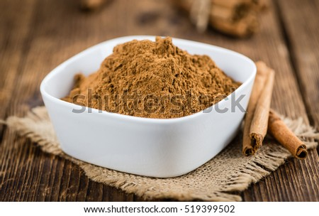 Cinnamon Powder as high detailed close-up shot on a vintage wooden table (selective focus)