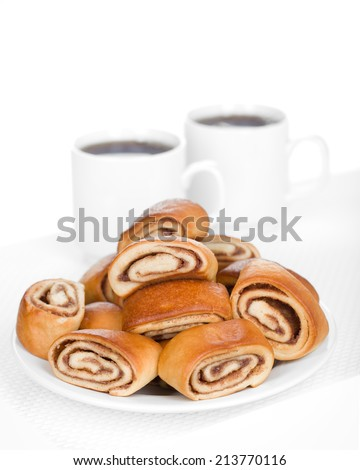 Cinnamon rolls on a plate with two cups of coffee / tea. - stock photo
