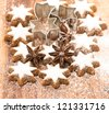 cinnamon stars and star anise on wooden background with sugar powder. christmas bakery - stock photo