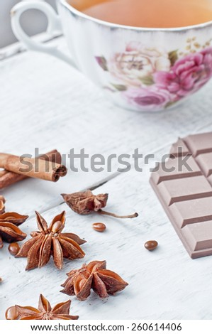 cinnamon stick, star anise, bar of chocolate and cup of tea on wooden table - stock photo