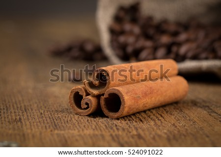 cinnamon sticks and coffee on hessian canvas with wooden background