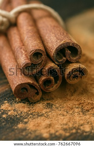 Cinnamon sticks and powder on rustic wooden Board closeup. Spices. Seasonings. Selective focus
