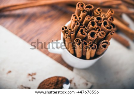 Cinnamon sticks and powder on rustic wooden board, top view