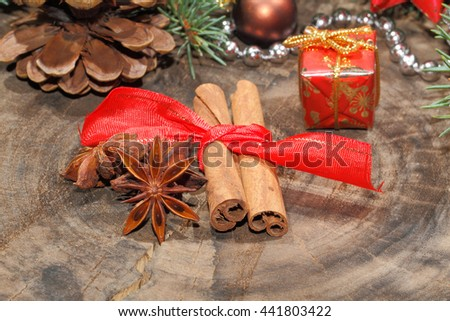 Cinnamon sticks, anise stars and christmas decoration on a rustic, wooden plate - stock photo