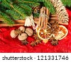 cinnamon sticks, anise stars and sliced of dried orange. christmas decoration with christmas tree branch. selective focus - stock photo