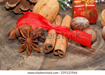 Cinnamon sticks, anise stars, nuts and christmas decoration on a rustic, wooden plate - stock photo