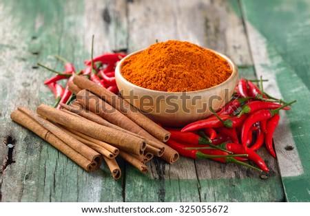 Cinnamon sticks  chili and  turmeric on wooden - stock photo