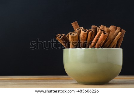 Cinnamon sticks, grouped in a ceramic green bowl on wood planked table, with black chalkboard background providing copy space.