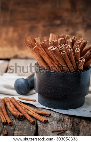 Cinnamon Sticks in a Stone Mortar on Wooden Table, rustic style - stock photo