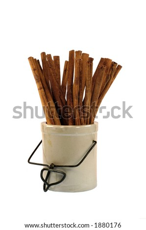 cinnamon sticks in earthenware jar on a white background - stock photo