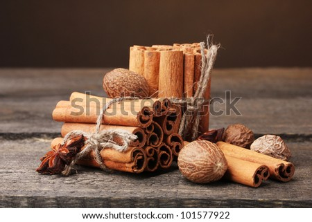 Cinnamon sticks, nutmeg and anise on wooden table on brown background - stock photo