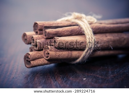 cinnamon sticks over dark wooden background at christmas time - stock photo