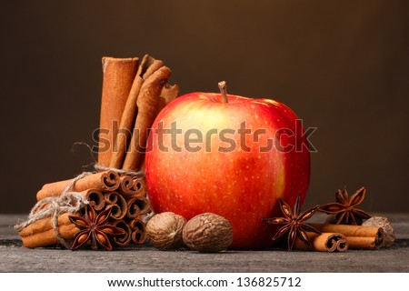 Cinnamon sticks,red apple, nutmeg,and anise on wooden table on brown background