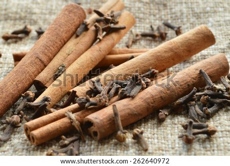 cinnamon sticks, spices, cloves on burlap background - stock photo