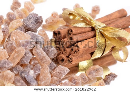 Cinnamon sticks with pure cane brown sugar on white background. Macro with extremely shallow dof. - stock photo