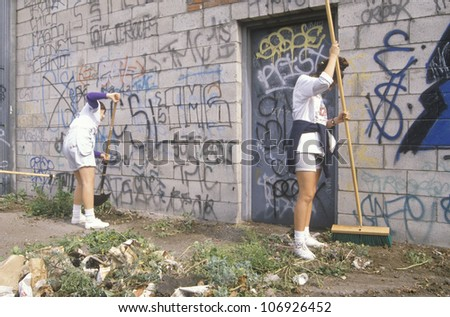 CIRCA 1990 - A group of young people participating in community cleanup by sweeping an alley - stock photo