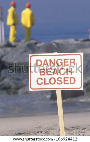 "CIRCA 1990 - A sign warning, ""Danger Beach Closed"" with cleanup crews in the background - stock photo"