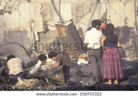 CIRCA 1992 - Family rummaging through home burned during riots, South Central Los Angeles, California - stock photo