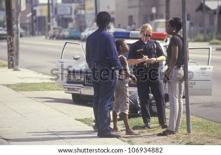 CIRCA 1992 - Policewoman taking a report, South Central Los Angeles, California - stock photo
