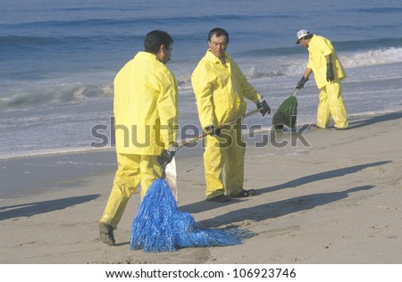 CIRCA 1990 - Three oil cleanup workers cleaning up the beach with adsorbent material after an oil spill covered Huntington Beach, California - stock photo