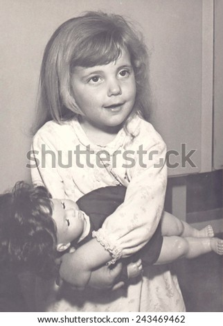 CIRCA 1968; vintage photograph of a young blonde girl in nightdress holding a doll - stock photo