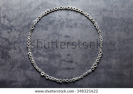 Circle from screw nuts on metal texture background