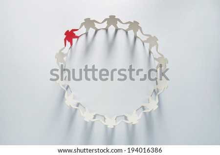 Circle of white business men paper cut-out figures with red leader standing out from the crowd - stock photo