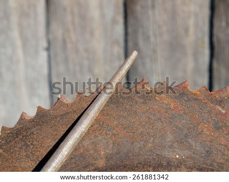 Circle saw teeth sharpening by round file close up - stock photo