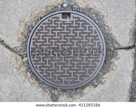 stock-photo-circle-steel-manhole-cover-on-concrete-street-in-japan-411285586.jpg