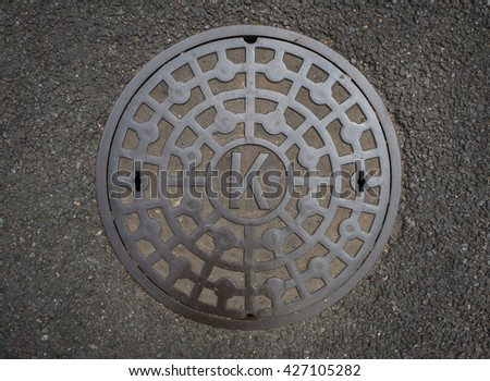 Circle steel manhole cover or sewer on asphalt street, this manhole shoot from Japan - stock photo