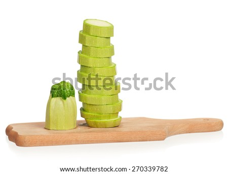 Circles of a green vegetable marrow put by a pyramid on a cutting board over white background - stock photo