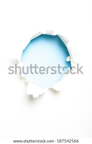 Circular hole on paper with torn sides on white background