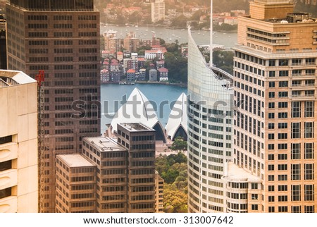 CIRCULAR QUAY, CENTRAL BUSINESS DISTRICT, SYDNEY, AUSTRALIA - DECEMBER 25, 2014: Sydney Opera House and close skyscrapers - view from Sydney Tower - warm orange tinted photograph - stock photo
