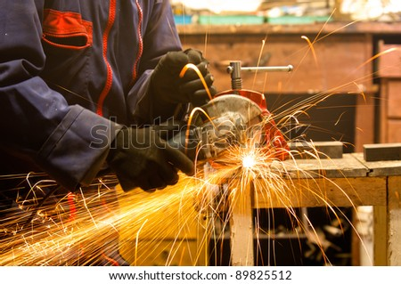 Circular saw and a worker in a hard job - stock photo