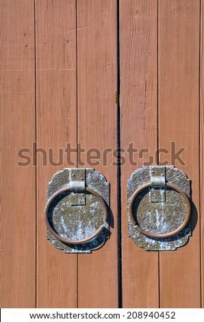 Circular vintage door handles on wood door - stock photo