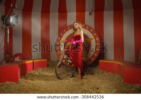 Circus actress in a red dress on retro bike